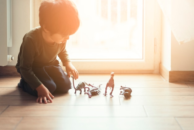 Kid playing with toy dinosaurs