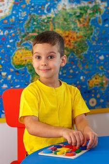 Ребенок играет с деревянной красочной головоломкой, концепция образования