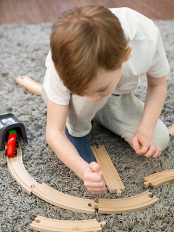 Kid playing with wooden roads and cars game on the floor