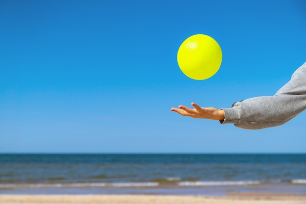 Kid playing with yellow beach ball on the sand by the sea water on a sunny day.