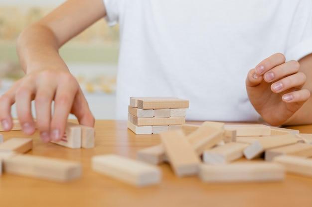 Bambino che gioca un primo piano del gioco della torre di legno