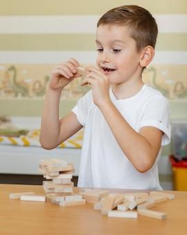 Kid giocando a un gioco di torre in legno