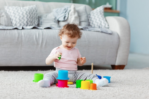 The kid plays on the floor on a light carpet with bright toys, builds a tower