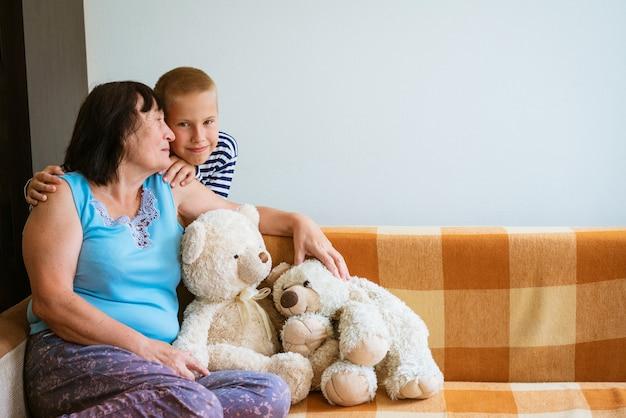 아이는 늙은 할머니와 테디베어 장난감을 가지고 노는 명랑하고 웃는 할머니와 그녀의 그랜드...