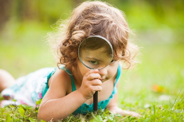 Kid plays with magnifying glass in the garden
