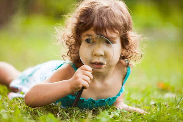 子供は庭で虫眼鏡で遊ぶ