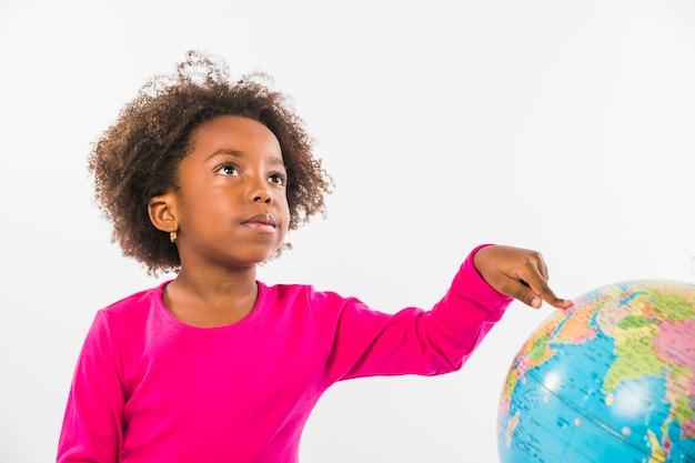 Kid pointing at globe in studio