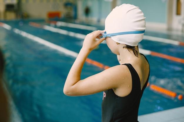 고글을 착용할 준비를 하는 아이. 그녀는 물 속으로 뛰어들려고 합니다. 스포츠, 취미.