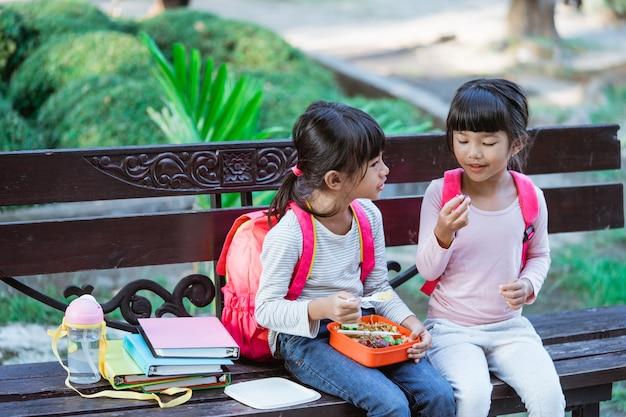 お弁当で食事を楽しんでいる小学生