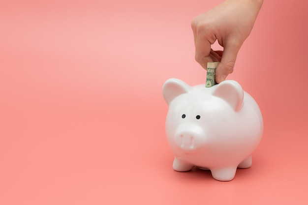 子供はピンクのパステル調の背景に貯金箱にお金を置きます。お金を節約。