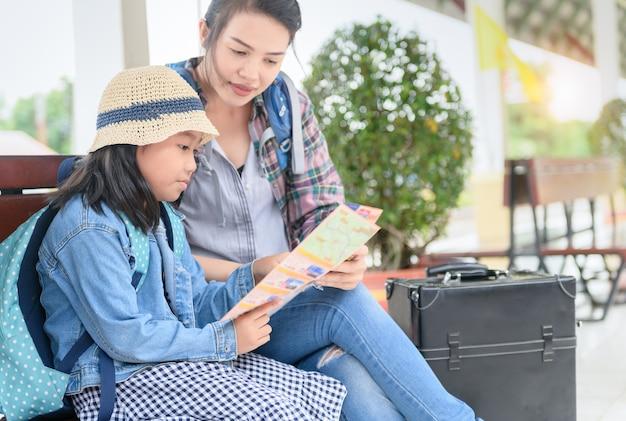 아이는 기차역에서 어머니와 함께지도를 읽었습니다.