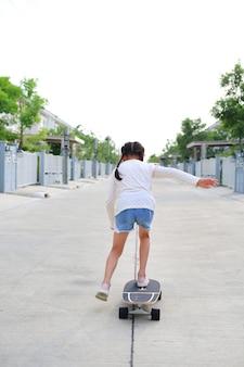 通りで屋外のスケートボードに乗っている子供。背面図