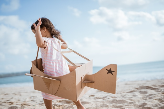 Kid run at the beach play with toy airplane made of cardboard