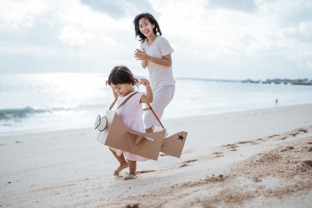 Kid running at the beach play with cardboard toy airplane