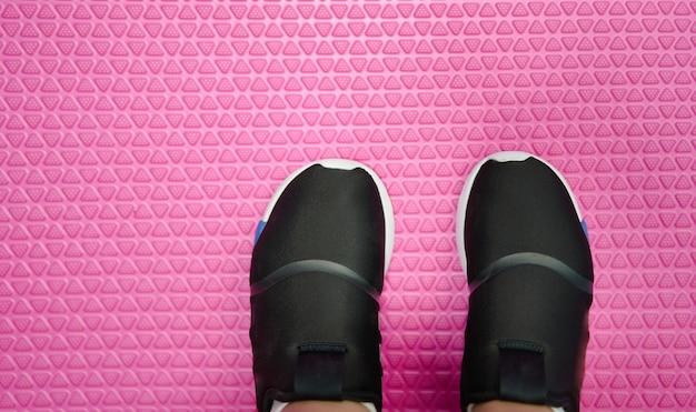 Kid running shoes wear on feet on texture mat floor top view