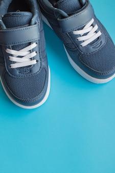 青色の背景に分離された子供の運動靴。背景色のカジュアルシューズのペア。スニーカーは、主にスポーツまたは他の形態の運動のために設計された靴です。青い靴。コピースペース