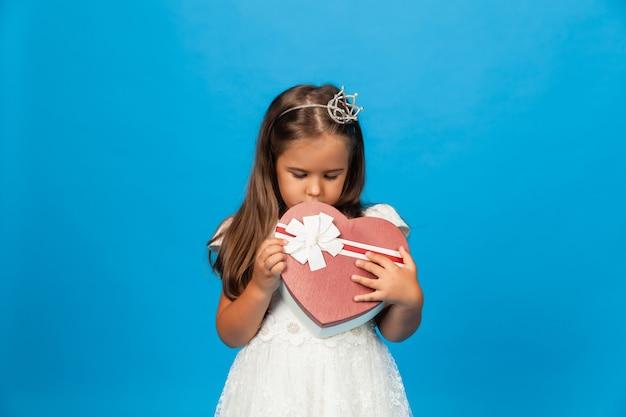 子供の誕生日プレゼント。サプライズとギフトボックス。贈り物の箱を持っている少女。
