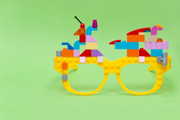 Kid's blocks building on yellow glasses on green table. educational and creativity concept.