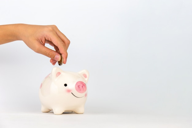 Kid's hand putting coin in piggy bank on white background