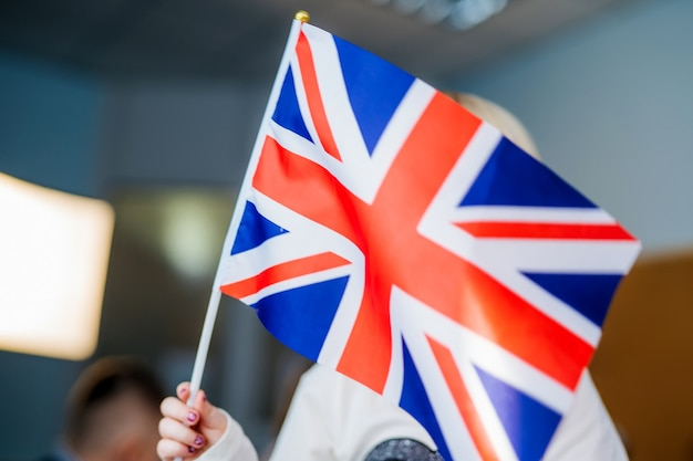 Kid's hands are holding england uk flag. studing foreign languages. english lesson. closeup.