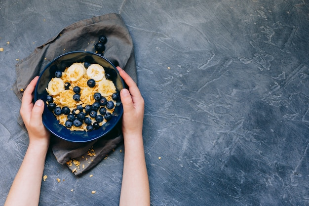 Kid's hands hold dark blue bowl of oatmeal porridge with banana and blueberry on vintage table top view in flat lay style. hot breakfast and homemade food. free space. homemade cuisine.