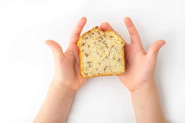 子供の手は、テキスト用のコピースペースと白い背景の上に焼きたての自家製全粒パンを保持しています。有機およびベジタリアン料理のコンセプト。