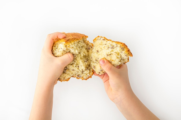 Kid's hands hold freshly baked homemade whole-grain bread on white background with copy space for text. organic and vegetarian food concept.