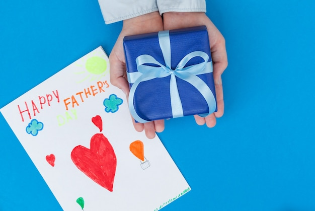 Kid's hands holding gift box with child's drawing on blue concept father's day greeting card