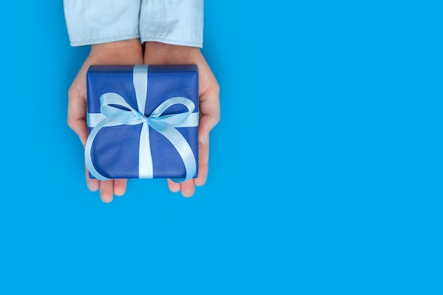 Kid's hands holding gift box wrapped in craft paper and tied with bow on blue concept father's day or birthday greeting card