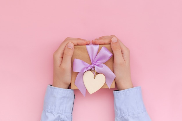 Kid's hands holding gift box wrapped in craft paper and tied with bow on pink wall valentines day concept.