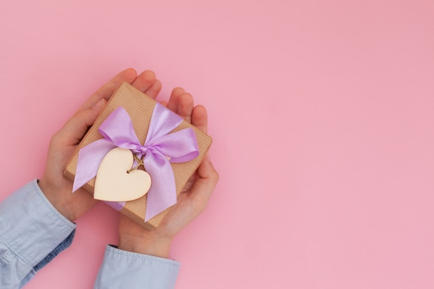 Kid's hands holding gift box wrapped in craft paper and tied with bow on pink wall.