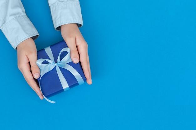 공예 종이에 싸서 파란색 개념 아버지의 날 또는 생일 인사말 카드에 활로 묶인 선물 상자를 들고 아이의 손
