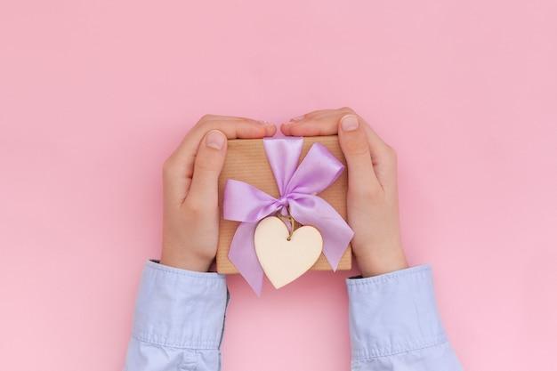クラフト紙で包まれ、ピンクの壁のバレンタインデーのコンセプトに弓で結ばれたギフトボックスを保持している子供の手。