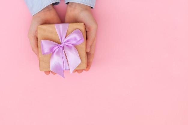 クラフト紙で包まれ、ピンクの壁に弓で結ばれたギフトボックスを持っている子供の手。