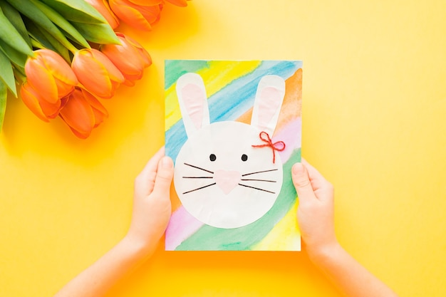 Kid's hands holding hand-made easter card and orange tulips on yellow background