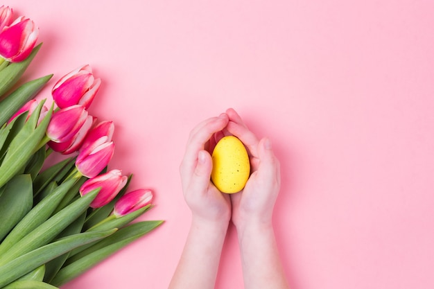Kid's hands holds yellow easter egg. easter holiday background with pink flowers tulips and free copy space. flat lay.