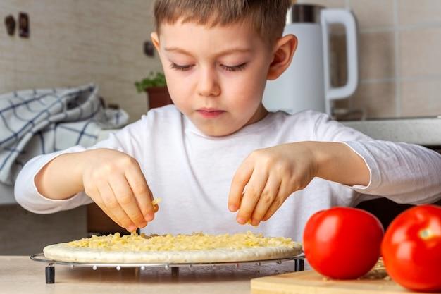아이의 손은 피자 반죽에 치즈를 뿌린다. 아이가 직접 만든 피자를 요리하는 과정. 미취학 아동의 기술, 작은 도우미. 가족 여가. 인공 노이즈, 선택적 포커스, 백라이트