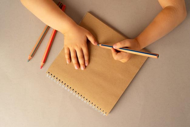 Детские руки писать в открытой записной книжке, вид сверху, копировать пространство
