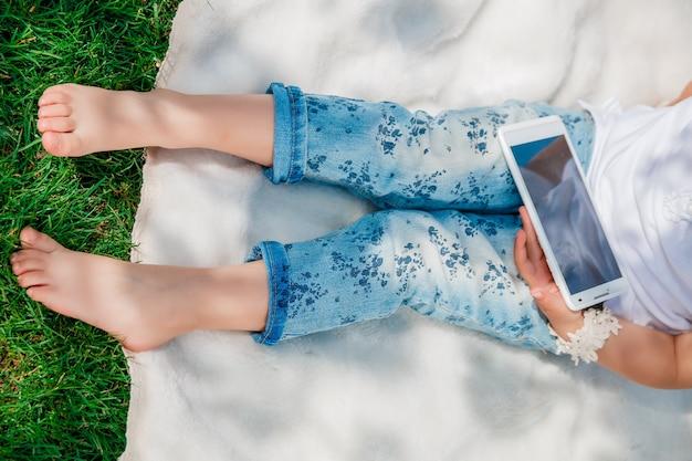 タブレット、スマートフォン、携帯電話で遊んだり教育したりする子供の足、上面図。認識できない女の赤ちゃん。