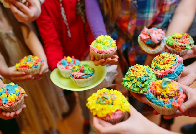 子供のパーティー。メガネでカップケーキをつなぐ子どもたち。