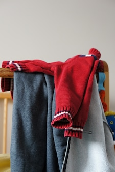 Kid's red  knitted sweater on a crib