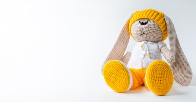 白い背景の上に座っている子供のおもちゃのぬいぐるみうさぎ。ぬいぐるみは児童保護のシンボルです。