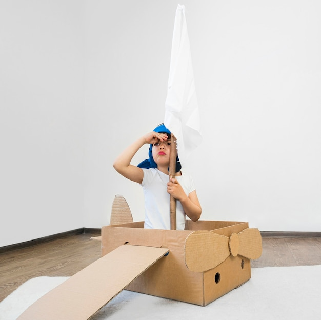 Kid sailing in cardboard boat