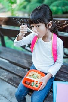 Kid school student enjoying eating her meal in lunch box during school break