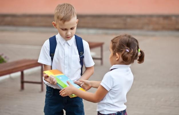 아이 남학생은 제복을 입은 여학생에게 교과서를 줍니다.