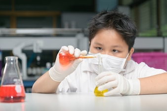 Kid scientist making experiment with test tube i
