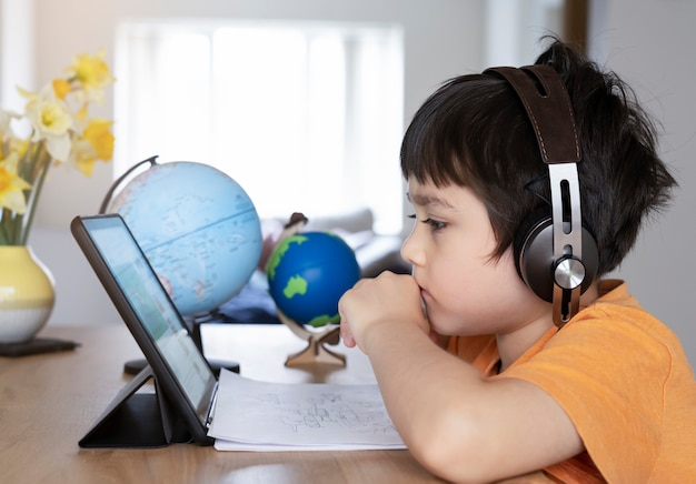 Kid self isolation using tablet for his homework, child doing  using digital tablet searching information on internet