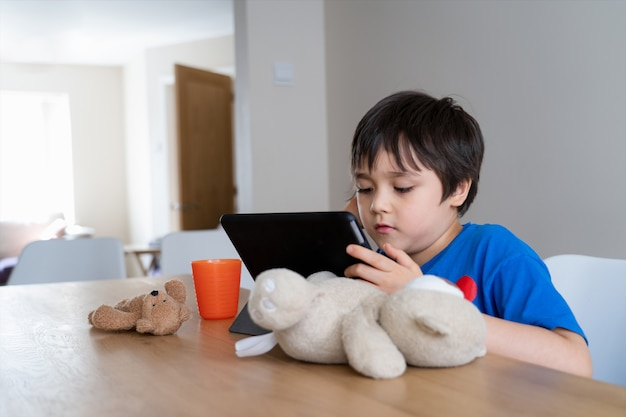 Kid self isolation using tablet for his homework