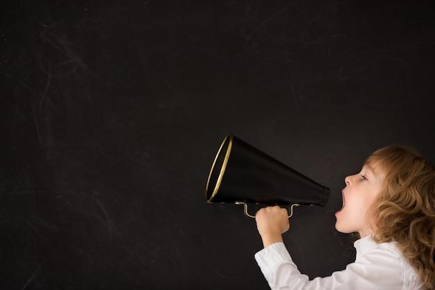 黒板に対してビンテージメガホンを通して叫ぶ子供