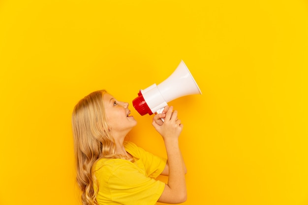 Kid shouting through vintage megaphone. communication concept. blue sky background as copy space for your text.